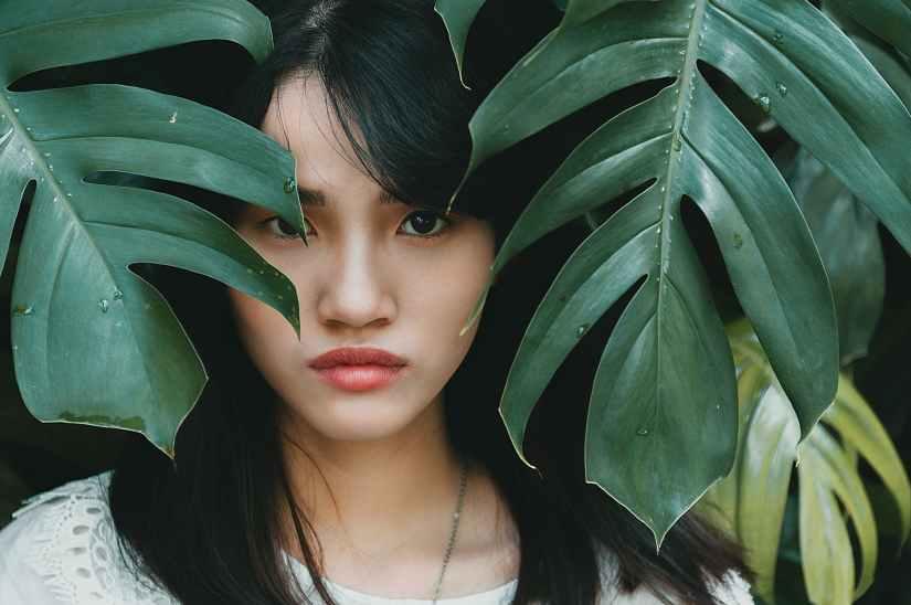 woman standing between green leaves