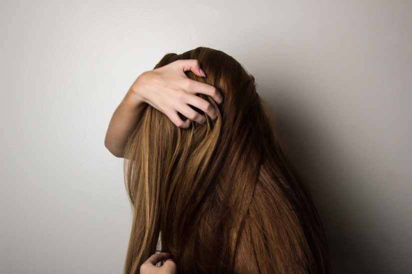 photo of woman covering face with her hair